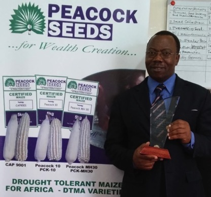 Felix Dumbe, Founder and President of Peacock Seeds, holding Peacock's CYMMIT award at Peacock headquarters in Lilongwe, Malawi