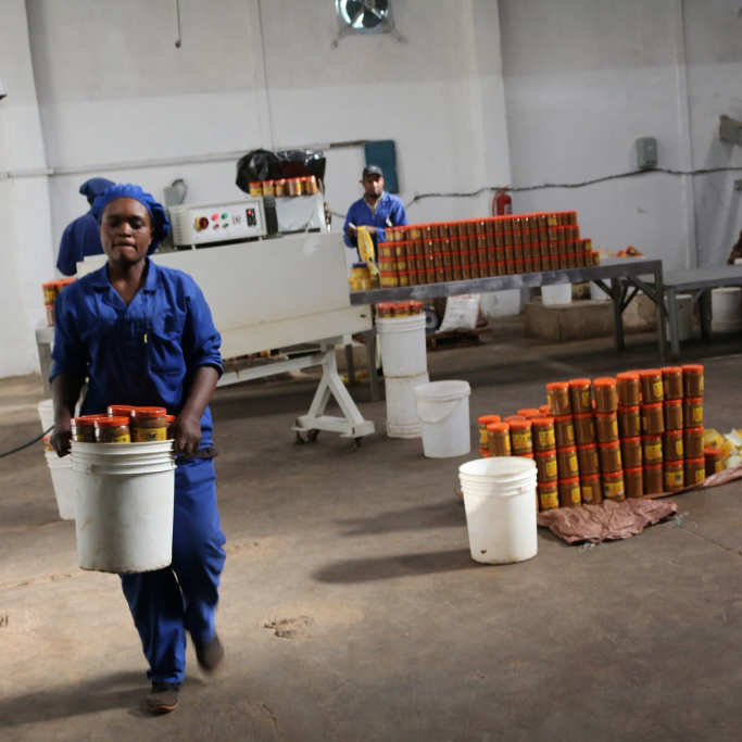 Photo: COMACO worker taking product to the packaging line